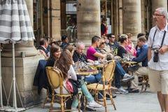 Les wagon-restaurants détendent aux tables de café au soleil sous les colonnes du Image libre de droits