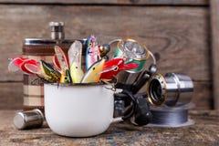 Les wobblers d'appâts dépassent de la tasse en métal blanc Photographie stock libre de droits