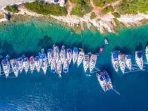 Les yachts ancored dans une baie avec la vue aérienne claire des eaux bleues Images libres de droits