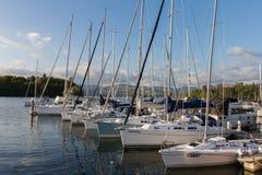 Les yachts de luxe de voile ont amarré le long d'un pilier dedans Bowness-sur-Windermere Image stock