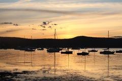 Les yachts et les bateaux ont amarré sur les eaux tranquilles au coucher du soleil Images libres de droits