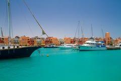 Les yachts ont amarré à quai au port de Hurghada, marina de Hurghada au coucher du soleil contre la mosquée Photos stock
