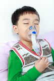 Les yeux fermants et les prises d'enfant asiatique de plan rapproché un masque vaporisent l'inhalateur Photo stock