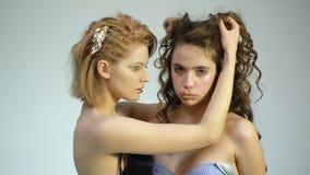 Lesben mit Gold bilden auf grauem Hintergrund Schönheit und Friseur Modische Frauen mit modernem goldenem Make-up stock video footage