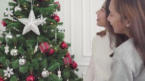 Lesbian Asian couple feeling happy decorating christmas tree in her living room at home in Christmas Festival. stock footage