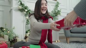 Lesbian Asian couple giving christmas gifts to each other in her living room at home in Christmas Festival. stock video footage