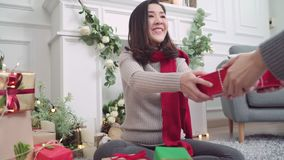 Lesbian Asian couple giving christmas gifts to each other in her living room at home in Christmas Festival. stock footage
