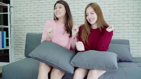 Lesbian Asian couple sing a song and dancing in living room at home, sweet couple enjoy funny moment. Lesbian Asian couple sing a song and dancing in living stock video footage