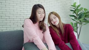 Lesbian Asian couple sing a song and dancing in living room at home, sweet couple enjoy funny moment. stock footage