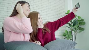Lesbian Asian couple using smartphone selfie in living room at home, sweet couple enjoy funny moment. Lesbian Asian couple using smartphone selfie in living stock footage