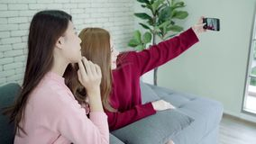 Lesbian Asian couple using smartphone selfie in living room at home, sweet couple enjoy funny moment. stock video