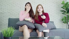 Lesbian Asian couple watching TV laugh and eating popcorn in living room at home, sweet couple enjoy funny moment. stock footage