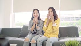 Lesbian Asian couple watching TV laugh in living room at home, sweet couple enjoy funny moment. Lesbian Asian couple watching TV laugh in living room at home stock video footage