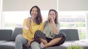 Lesbian Asian couple watching TV laugh in living room at home, sweet couple enjoy funny moment while lying on the sofa. Lesbian Asian couple watching TV laugh stock video