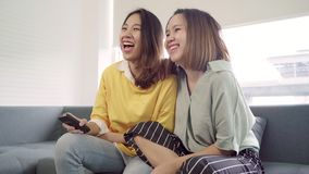 Lesbian Asian couple watching TV laugh in living room at home, sweet couple enjoy funny moment while lying on the sofa. Lesbian Asian couple watching TV laugh stock video footage