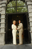 Lesbian brides in front of town hall. Happy mature lesbian couple posing at the entry of town hall after official marriage ceremony in formal dress Royalty Free Stock Photos