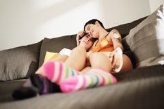 Lesbian Couple With Colorful Socks Embracing On Sofa At Home stock image