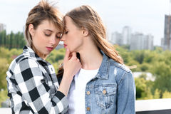 Lesbian couple embracing embracing and able to kiss with eyes closed. Casual lesbian couple embracing embracing and able to kiss with eyes closed Royalty Free Stock Image