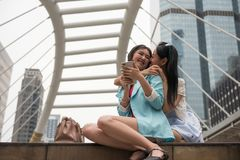 Lesbian couple hug and kiss in city. Two sweet lesbian couple hug and kiss at urban Bangkok ciy. women surprise girlfriend by holding and kissing while she play Royalty Free Stock Image
