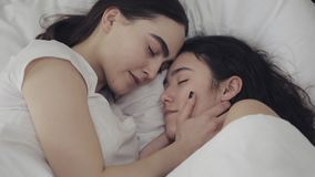 Lesbian couple hugging and smiling while lying together in bed at home. Young lesbians kisses and hugs after wake up.  stock video footage