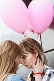 Lesbian couple kissing and holding air balloons outdoors. Young lesbian couple kissing and holding air balloons outdoors Stock Images