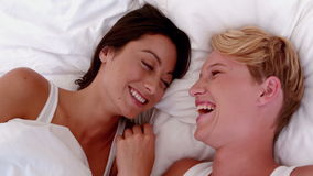 Lesbian couple laughing in bed