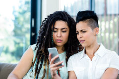 Lesbian couple looking at mobile phone Stock Photo