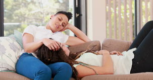 Lesbian couple lying together on the couch stock footage