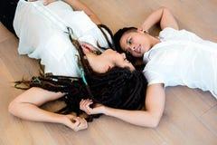 Lesbian couple lying on wooden floor Stock Photo