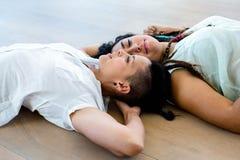 Lesbian couple lying on wooden floor Royalty Free Stock Photos