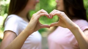Lesbian couple making heart with hands, open relationship in same-sex love. Stock photo stock image