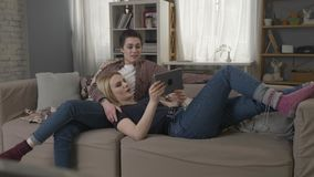 Lesbian couple is resting on the couch, laughing and watching funny movie on tablet 60 fps. 4k stock video footage