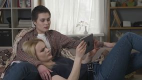 Lesbian couple is resting on the couch, using tablet computer, scrolling photos on tablet, holding hands, smiling. Talking, family idyll, 60 fps 4k stock video