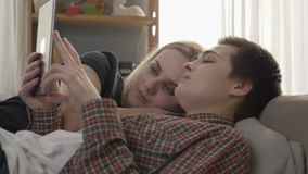 Lesbian couple is resting on the couch, using tablet computer, scrolling photos on tablet, smiling, family idyll, love. Cute, close up 60 fps 4k stock footage