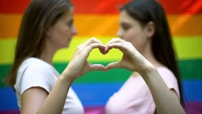 Lesbian couple showing love sign, standing against rainbow flag background stock images