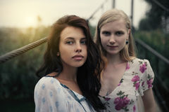 Lesbian Couple Together Outdoors Concept. Two beautiful young girlfriends blonde and brunette embracing on lake bridge on evening sunst. Rural scene. Women Royalty Free Stock Image