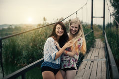 Lesbian Couple Together Outdoors Concept. Two beautiful young girlfriends blonde and brunette embracing on lake bridge on evening sunst. Rural scene. Women Stock Photo