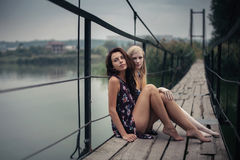 Lesbian Couple Together Outdoors Concept. Two beautiful young girlfriends blonde and brunette sitting on lake bridge on evening sunst. Rural scene. Women Stock Photo