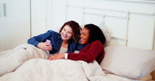 Lesbian couple using mobile phone on bed stock video