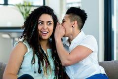 Lesbian couple whispering in ear Stock Photo