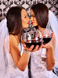 Lesbian couples in wedding bridal dress kissing and drinking red wine. Royalty Free Stock Images