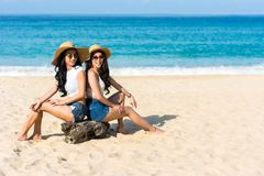 Lesbian couplesare sitting on the beach. Lesbian couples or close friends are sitting on the beach While relaxing vacation or weekend on sunny days and nice Stock Photo