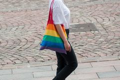 Lesbian girl walking in the street with rainbow bag stock photo