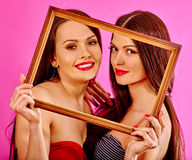 Lesbian women holding  art frame. Near her faces. Pink background Stock Photos