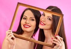 Lesbian women holding  art frame. Royalty Free Stock Images
