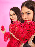 Lesbian women holding heart symbol. Lesbian women holding red heart symbol. Erotic foreplay game Royalty Free Stock Photos