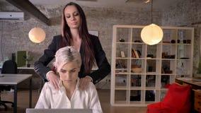 Lesbiana joven que da masajes a su colega femenino en la oficina moderna, mujer que liga con la mujer almacen de metraje de vídeo