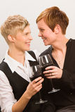 Lesbians and red wine. Two happy lesbians and a glass of red wine, vertical format Royalty Free Stock Images