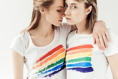 Lesbians in white shirts with printed rainbow. Portrait of lesbians in white shirts with printed rainbow isolated on white Royalty Free Stock Image