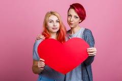 Lesbiennes tenant un coeur rouge à un niveau de coffre sur un fond rose Photographie stock libre de droits